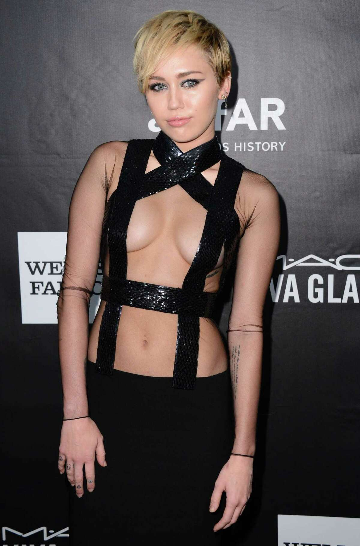 In this Oct. 29, 2014 photo, Miley Cyrus arrives at the 2014 amfAR Inspiration Gala at Milk Studios in Los Angeles.