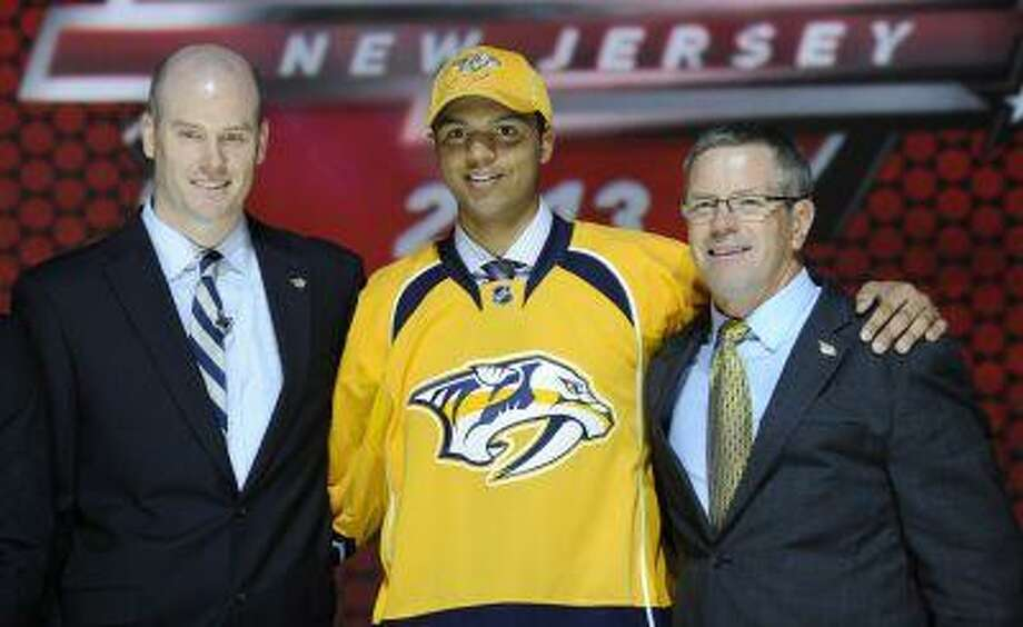 Seth Jones, a defenseman, stands with officials from the Nashville Predators sweater after being chosen 4th overall in the first round of the NHL hockey draft, Sunday, June 30, 2013, in Newark, N.J. Photo: ASSOCIATED PRESS / AP2013