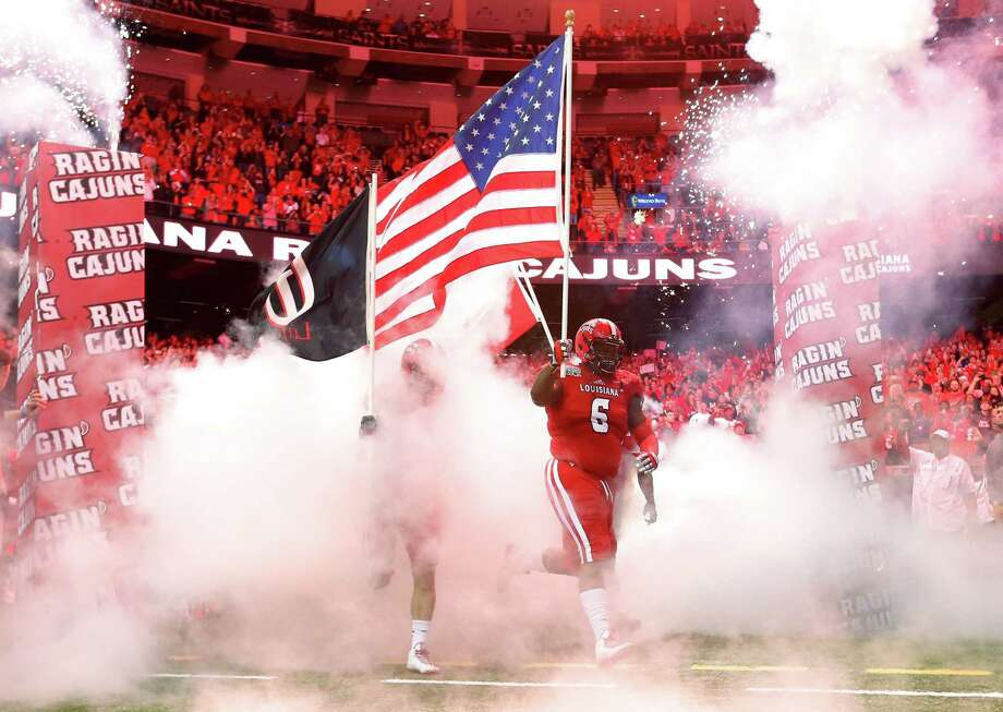 Louisiana-Lafayette defensive lineman Justin Hamilton carries an American flag out to the field before the New Orleans Bowl against Nevada on Saturday. Photo: Jonathan Bachman — The Associated Press  / FR170615 AP