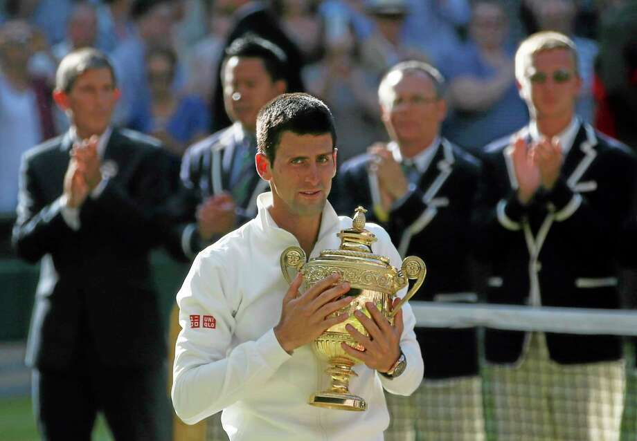 Novak Djokovic holds the trophy after defeating Roger Federer in the men's singles final at Wimbledon on Sunday. Photo: Pavel Golovkin — The Associated Press  / AP