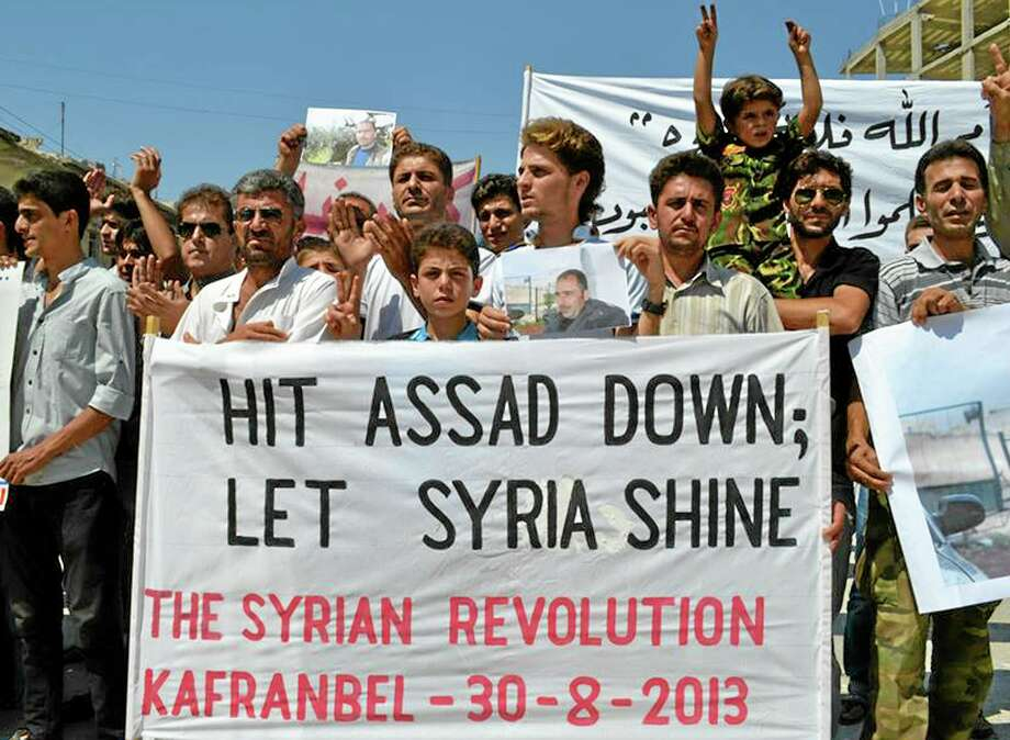 """In this picture taken on Friday, Aug. 30, 2013, citizen journalism image provided by Edlib News Network, ENN, which has been authenticated based on its contents and other AP reporting, anti-Syrian regime protesters carry a banner during a demonstration at Kafr Nabil town in Idlib province, northern Syria. The U.N. experts investigating last week's alleged chemical weapons strike outside Damascus left Syria and crossed into neighboring Lebanon early Saturday, departing hours after President Barack Obama said he is weighing """"limited and narrow"""" action against a Syrian regime that the administration has accused of launching the deadly attack. (AP Photo/Edlib News Network ENN) Photo: AP / EDLIB NEWS NETWORK ENN"""