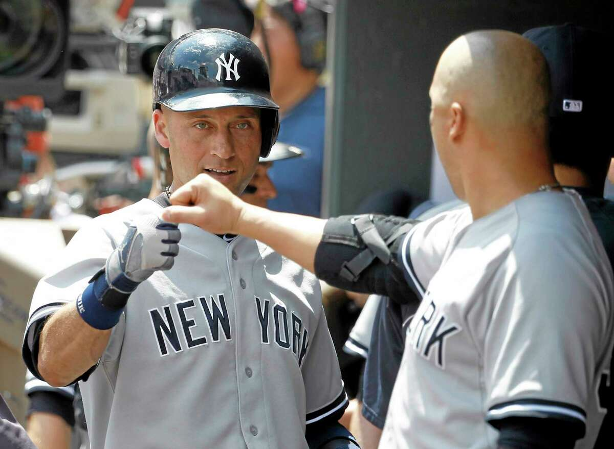 The Yankees' Carlos Beltran, right, congratulates Derek Jeter after Jeter's sacrifice fly in the second inning on Sunday.