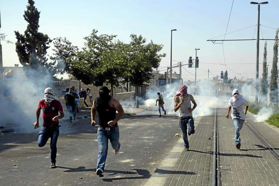 Palestinians run away from tear gas as they clash with Israeli security forces during the funeral of 16-year-old Mohammed Abu Khdeir in Jerusalem on Friday. Israeli police clashed with Palestinian protesters in Jerusalem on Friday as thousands of people converged on a cemetery for the burial of an Arab teenager, who Palestinians say was killed by Israeli extremists in a suspected revenge attack. Photo: Associated Press  / AP