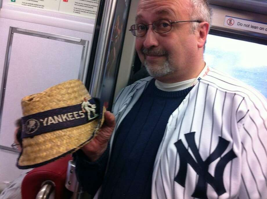 New York Yankees fan Bob Madar of Trumbull shows off his father's old 1960 Yankees straw hat while riding the Metro-North train to the game Mark Zaretsky/Register