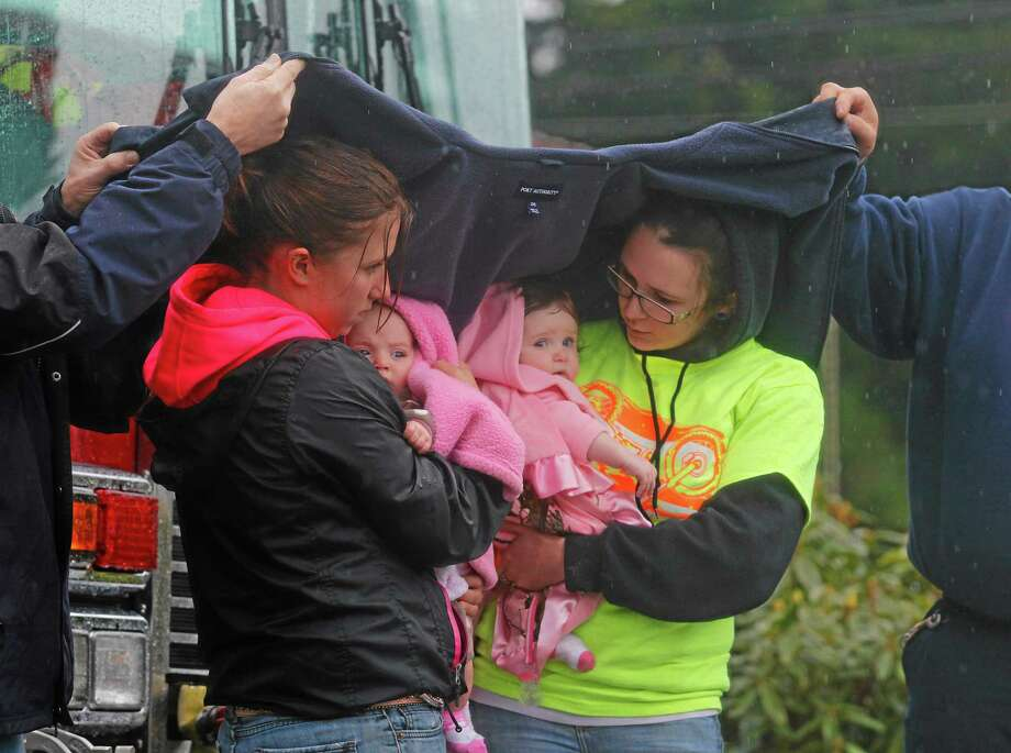 Volunteer Ralph Jones, left, and Tim Perciful, right, of the Mountainview, Black Diamond Fire Department, help keep Klarissa Calviste and her daughter Kielie Braaten, left, and Brooke Odenius and her daughter Bexli dry as they observe a state-wide moment of silence to honor the victims of the Oso mud slide in front of the Darrington, Wash. Fire Department on Saturday, March 29, 2014. (AP Photo/ The Herald, Annie Mulligan) Photo: AP / Annie Mulligan / The Herald