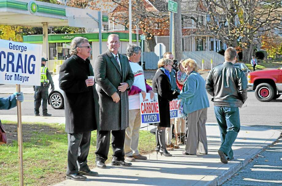 Candidates and campaign workers greet voters outside of the Torrington Armory Tuesday morning. Photo: John Berry—Register Citizen