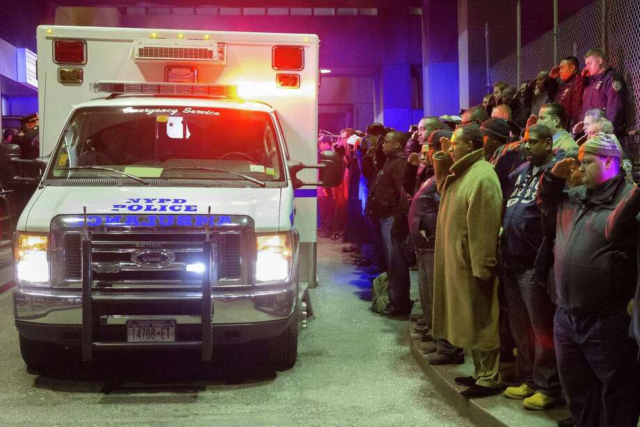 Mourners stand at attention as the bodies of two fallen NYPD police officers are transported from Woodhull Medical Center, Saturday, Dec. 20, 2014, in New York. Photo: (John Minchillo — The Associated Press) / FR170537 AP
