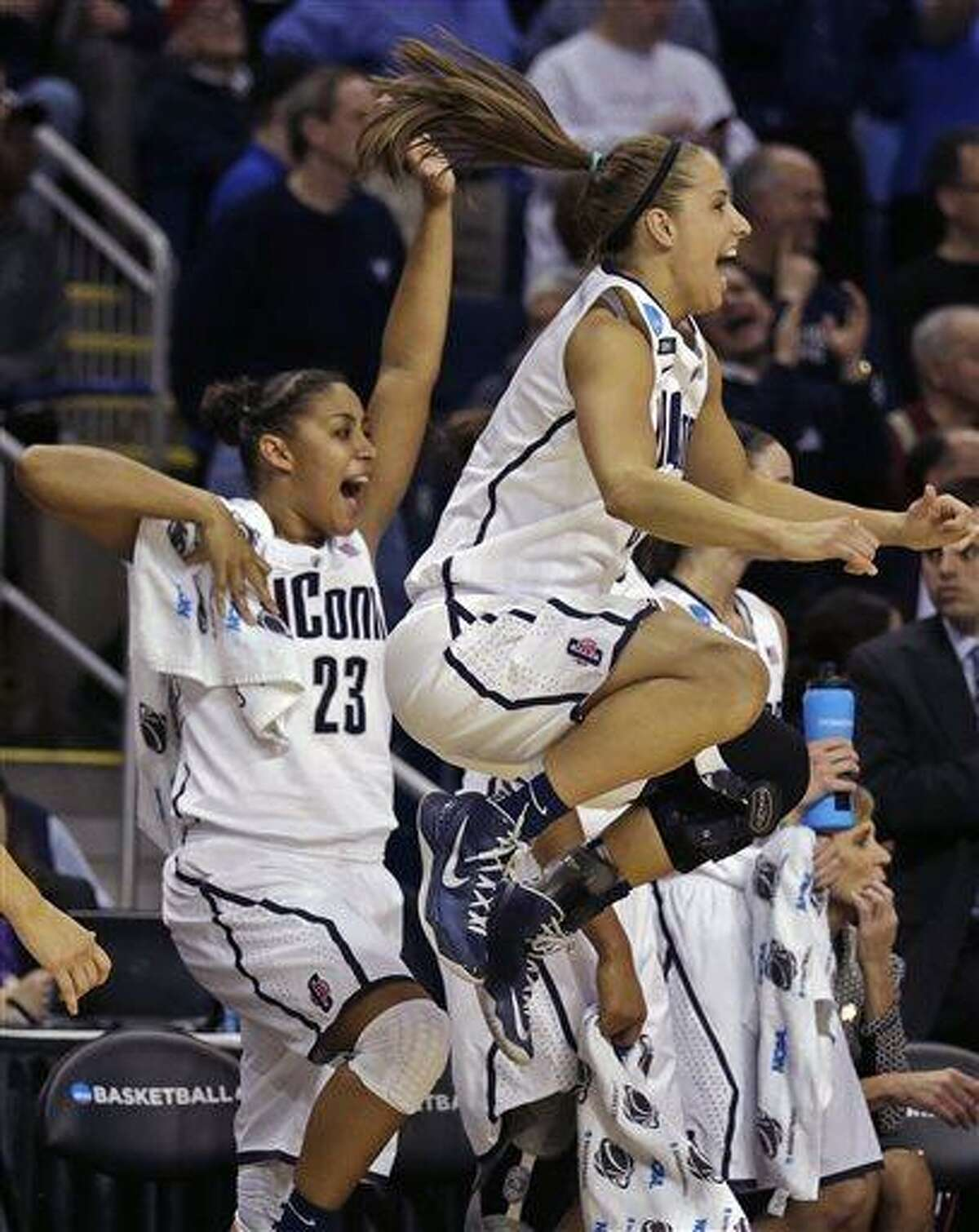 Connecticut guard Caroline Doty, right, leaps in the air as she celebrates with teammate Kaleena Mosqueda-Lewis (23) in the final seconds of the second half of a women's NCAA regional final basketball game against Kentucky in Bridgeport, Conn., Monday, April 1, 2013. Connecticut won 83-53 and advances to the Final Four. (AP Photo/Charles Krupa)