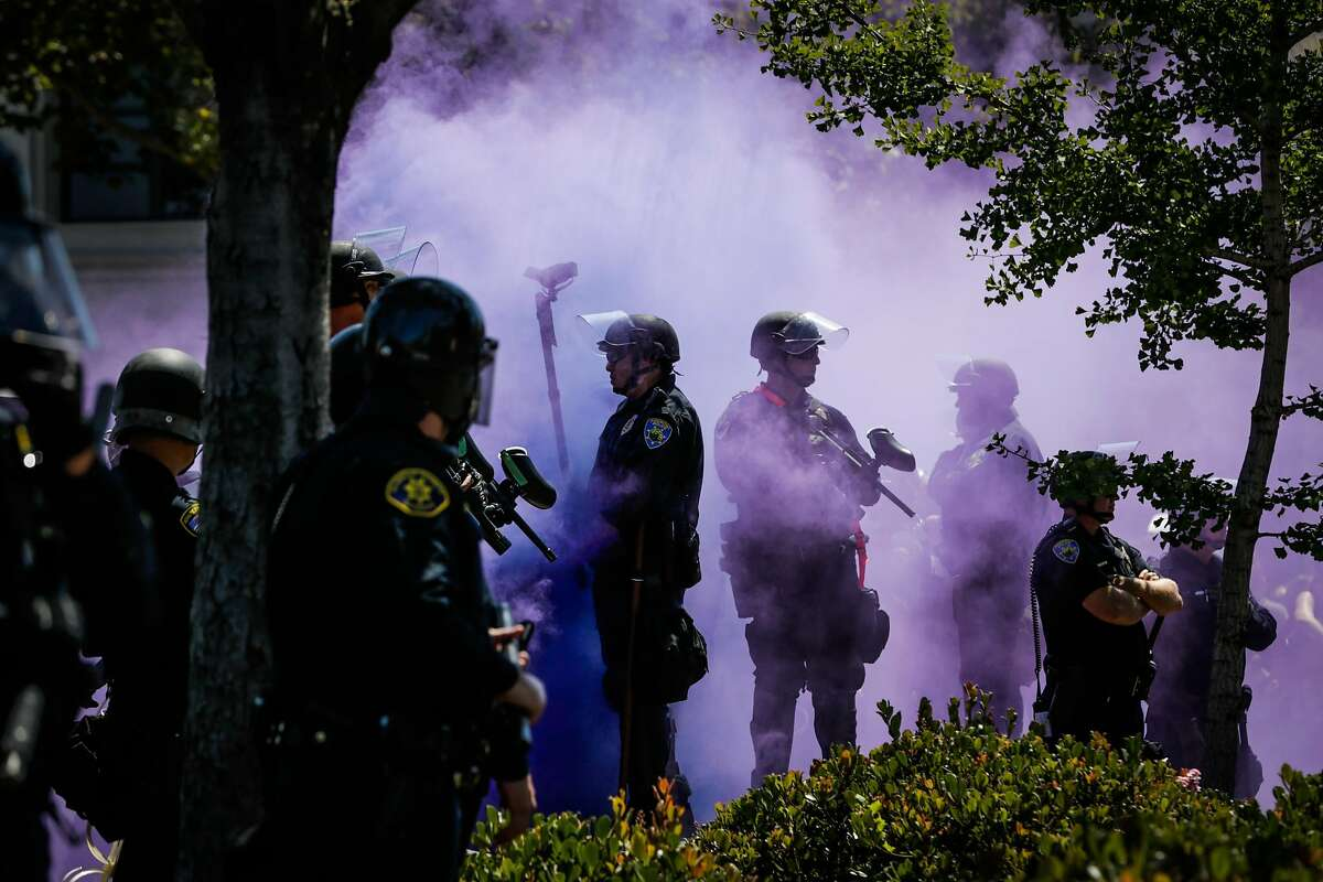 Police officers are covered in a purple smokebomb haze on Martin Luther King Jr. Way and Allston Way during a protest in Berkeley, Calif., on Sunday, August 27th, 2017.