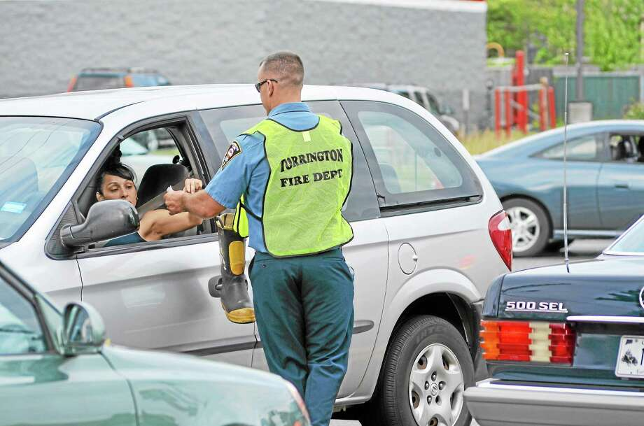A firefighter accepts a donation from a driver on Thursday, Aug. 29, as the Torrington Fire Department participated in the national Fill-the-Boot to raise money for the Muscular Dystrophy Association. Photo: Tom Caprood—Register Citizen