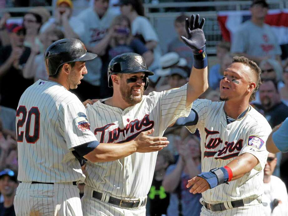 The Minnesota Twins' Chris Colabello, left, and Oswaldo Arcia, right, celebrate with Trevor Plouffe, center, after Plouffe grounded into a fielder's choice and Josh Willingham scored the winning run on a throwing error by New York Yankees catcher Francisco Cervelli during the eleventh inning of Saturday's game in Minneapolis. Photo: Ann Heisenfelt — The Associated Press  / FR13069 AP