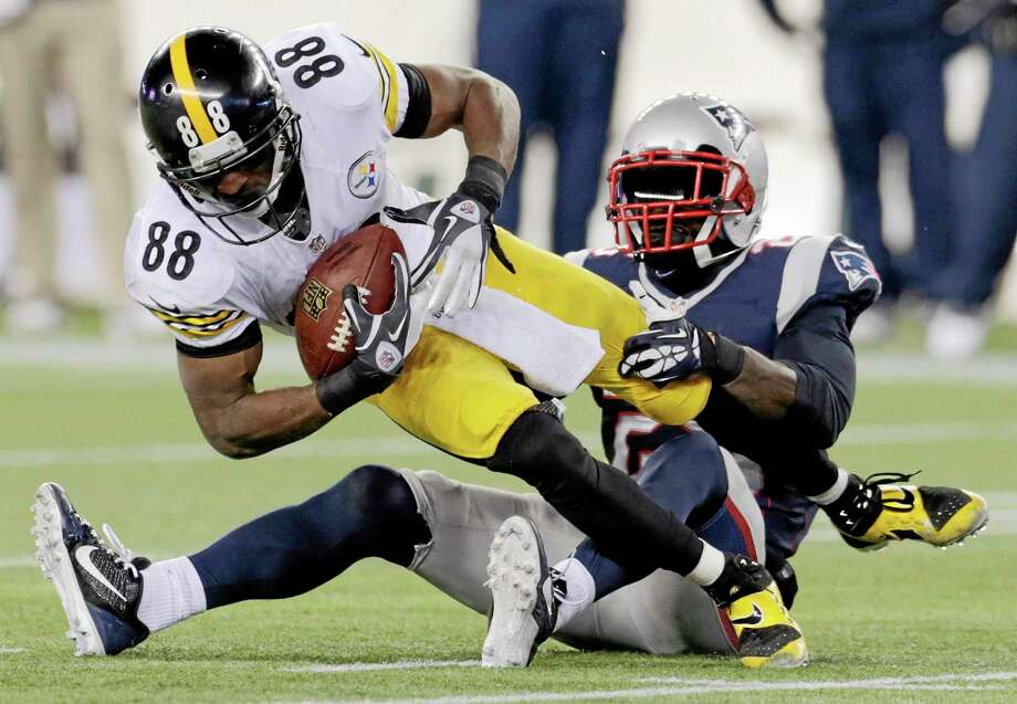 New England Patriots cornerback Kyle Arrington, right, tackles Pittsburgh Steelers wide receiver Emmanuel Sanders (88) in the fourth quarter Sunday. Photo: Charles Krupa — The Associated Press  / AP