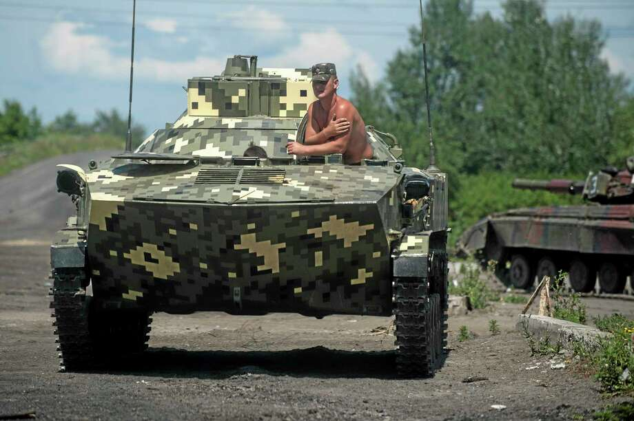A Ukrainian paratrooper sits in an APC at a checkpoint near Slovyansk, eastern Ukraine, Saturday, July 5, 2014. Ukraine's forces claimed a significant success against pro-Russian insurgents on Saturday, chasing them from one of their strongholds in the embattled east of the country. Rebels fleeing from the city of Slovyansk vowed to regroup elsewhere and fight on.  (AP Photo/Evgeniy Maloletka) Photo: AP / AP