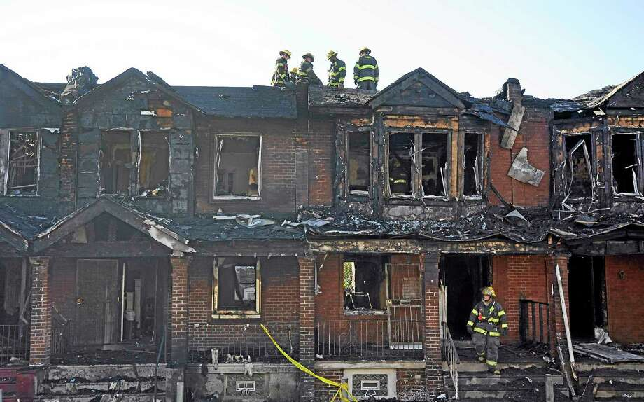 Philadelphia firefighters work on burned row homes on Saturday, July 5, 2014, in Philadelphia. Authorities say the fast-moving fire early Saturday has killed four children. Fire department officials say there is no immediate word on how many others were injured in the blaze that destroyed eight homes in the row and engulfed a total of 10 houses. (AP Photo/Michael Perez) Photo: AP / FR168006 AP