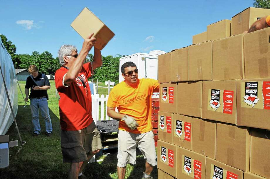 About 250 volunteers gathered at Lime Rock Park Saturday to assemble and pack 24,000 meals that will be donated to local food banks in the Northwest Corner, western Massachusetts and Dutchess County, N.Y., through the Drive to End Hunger program with assistance from race car driver Jeff Gordon. Photo: Laurie Gaboardi — Register Citizen