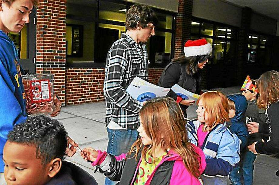 AMANDA WEBSTER — REGISTER CITIZEN Gilbert School students handed out donated books to Winsted elementary school students after performing holiday music concert on Friday. Photo: Journal Register Co.