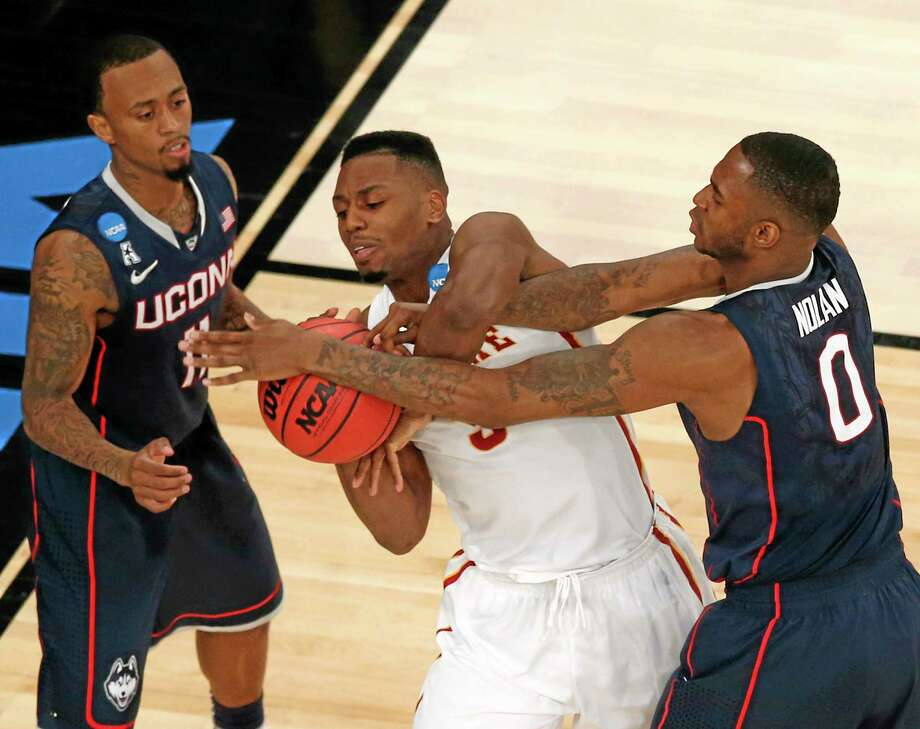 Iowa State's Melvin Ejim, center, struggles with Connecticut's Phillip Nolan, right, for the ball, with Connecticut's Ryan Boatright nearby during the second half in a regional semifinal at the NCAA men's college basketball tournament Friday, March 28, 2014 in New York. (AP Photo/Julio Cortez) Photo: AP / AP