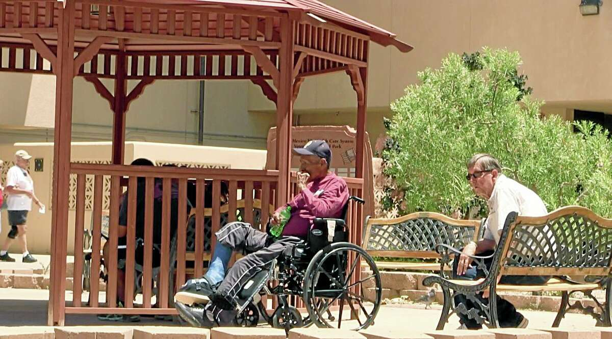 Men sit outside the Raymond G. Murphy VA Medical Center in Albuquerque, N.M., Thursday, July 3, 2014. A veteran who collapsed in an Albuquerque Veteran Affairs hospital cafeteria 500 yards from the emergency room, died Monday, June 30, 2014, after waiting 30 minutes for an ambulance, officials confirmed Thursday. Officials at the hospital said it took a half an hour for the ambulance to be dispatched and take the man from one building to the other, which is about a five minute walk. (AP Photo/Russell Contreras)