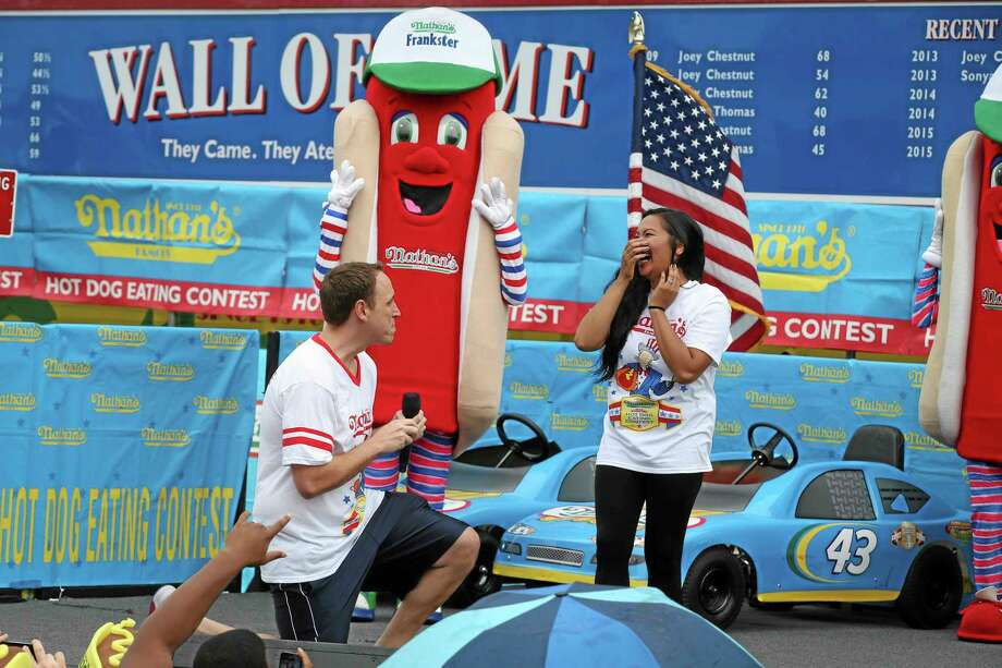 Competitive eater Joey Chestnut proposes to his girlfriend and fellow competitor Neslie Ricasa before the Nathan's Famous Fourth of July International Hot Dog Eating contest at Coney Island, Friday, July 4, 2014, in New York. Chestnut won his competition and eighth consecutive contest by finishing 61 hot dogs and buns. Photo: (John Minchillo — The Associated Press) / FR170537 AP