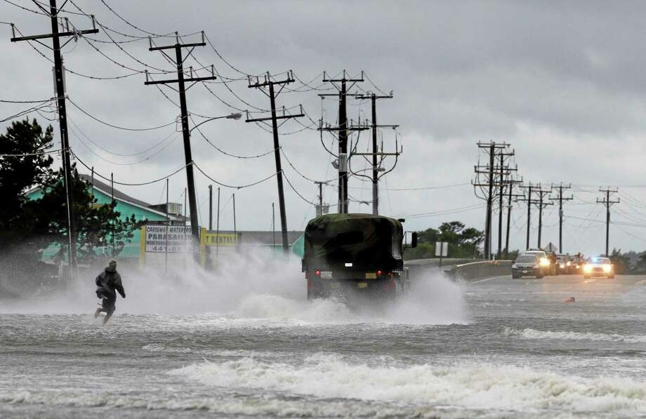 A military vehicle and a man navigate a flooded Highway 64 as wind pushes water over the road while Hurricane Arthur passes through Nags Head, N.C., Friday, July 4, 2014. (AP Photo/Gerry Broome) Photo: AP / AP
