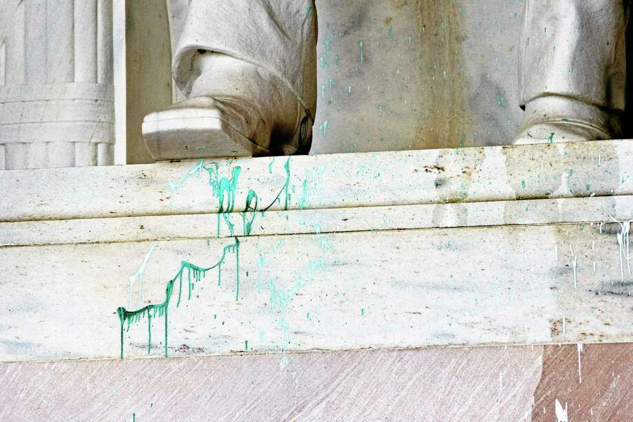 FILE - This July 26, 2013 file photo shows green paint splattered on the base of the statue of Abraham Lincoln at the Lincoln Memorial in Washington. A woman charged with defacing the Washington National Cathedral with green paint and suspected of similar vandalism at the Lincoln Memorial and other sites has been admitted to a hospital psychiatric ward.  A lawyer for Jiamei Tian told a judge during a hearing Thursday that if Tian's metal condition stabilizes, she can go back to a halfway house where she has been staying. The lawyer, Nancy Glass, didn't elaborate on concerns about Tian's mental health. Another status hearing in the case was set for Sept. 18.  (AP Photo/J. Scott Applewhite, File) Photo: AP / AP