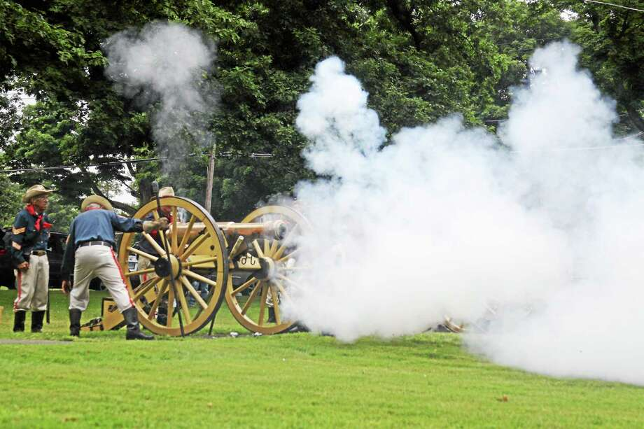 Reenactors fire the cannon as the First Litchfieldís Artillery Regiment celebrates July Fourth on the Litchfield green, despite impending rain. Kathryn Boughton - The Litchfield County Times Photo: Journal Register Co.