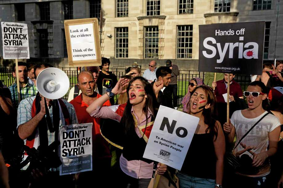 "People take part in a protest organized by the Stop the War coalition calling for no military attack on Syria from the U.S., Britain or France, across the road from the entrance of Downing Street in London, Wednesday, Aug. 28, 2013.  Britain said it would seek U.N. Security Council backing Wednesday for a measure condemning Syria for an alleged chemical attack against its civilians and authorizing ""appropriate measures"" in response. The resolution could be used to authorize military force against Syria.  (AP Photo/Matt Dunham) Photo: AP / AP"