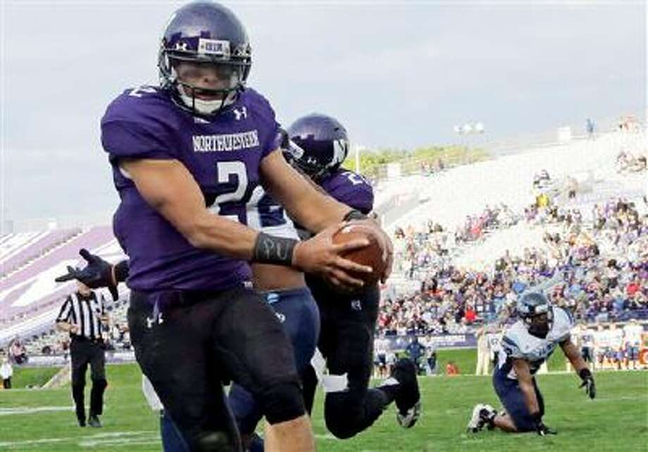 """FILE - In this Sept. 21, 2013 file photo, Northwestern quarterback Kain Colter (2), wears APU for """"All Players United"""" on wrist tape as he scores a touchdown during an NCAA college football game against Maine in Evanston, Ill. The decision to allow Northwestern football players to unionize raises an array of questions for college sports. Among them, state schools vs. public schools, powerhouse programs vs. smaller colleges.  (AP Photo/Nam Y. Huh, File) Photo: AP / AP"""