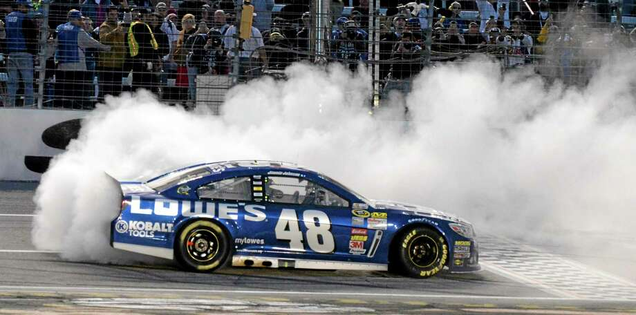 Jimmie Johnson (48) burns his tires after winning at Texas Motor Speedway in Fort Worth, Texas on Sunday. Photo: Larry Papke — The Associated Press  / FR58581 AP