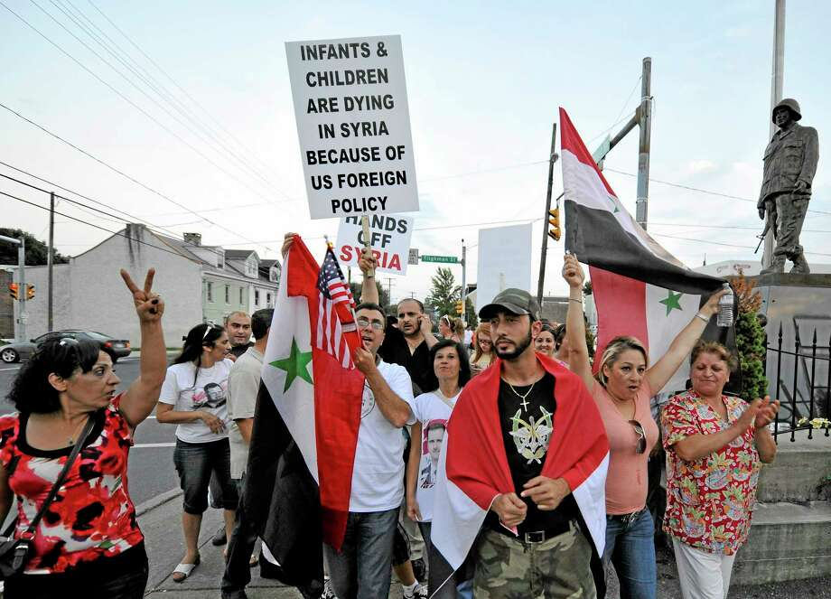 Members of the local Syrian community rally against the United States' involvement in Syria, Tuesday, Aug. 27, 2013 in Allentown, Pa. The United States, Britain and France have made it clear they believe the government of Syrian President Bashar Assad was behind a recent deadly chemical weapons attack in the suburbs of Damascus, and that such an act demands a swift international response. (AP Photo/Chris Post) Photo: AP / FR170581 AP