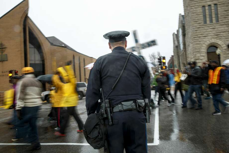 As a Jefferson City police officer watches from the sidewalk, protestors move along Monroe Street inside the Jefferson City limits while making their way into Missouri's capitol Dec. 5. Photo: File Photo  / The Jefferson City News-Tribune