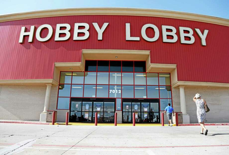"""FILE - This June 30, 2014, file photo shows customers walking into a Hobby Lobby store in Oklahoma City. There may be more to that """"we the people"""" notion than you thought.These are boom times for the concept of """"corporate personhood."""" Corporations are people? Mitt Romney got mocked during the 2012 presidential campaign for the very idea. But it turns out the principle has been lurking in U.S. law for more than a century, and the Supreme Court, in a 5-4 ruling, gave it more oomph this week when it ruled that certain businesses are entitled to exercise religious rights just as do people. (AP Photo/Sue Ogrocki, File) Photo: AP / AP"""