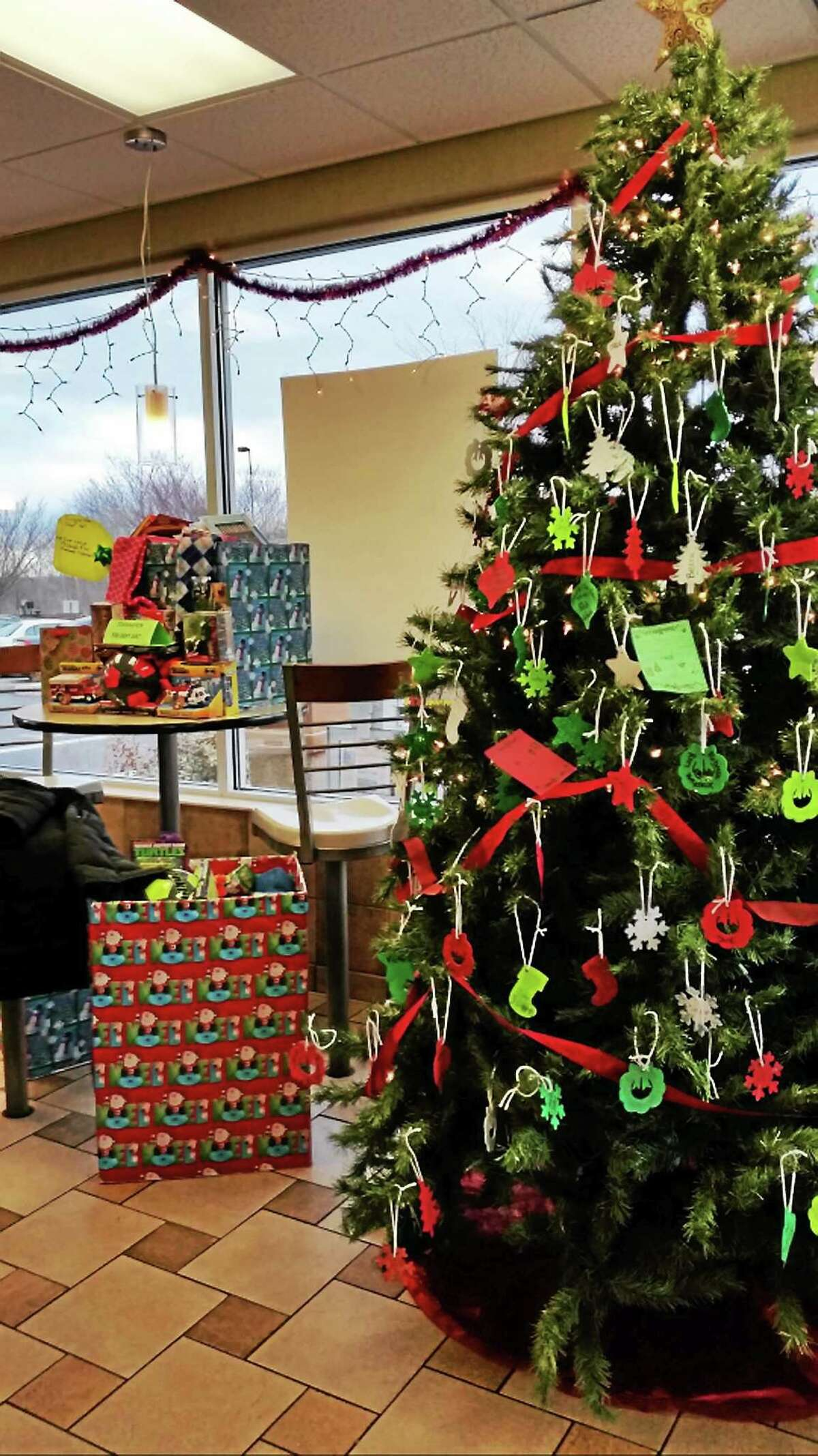 Amanda Webster/Register Citizen The Christmas tree at McDonald's in Torrington was decked out with ornaments handmade by employees. The ornaments were sold for $1 and the money was used to buy holiday gifts, which were then donated to local charities during a ceremony on Thursday, Dec. 18, 2014.