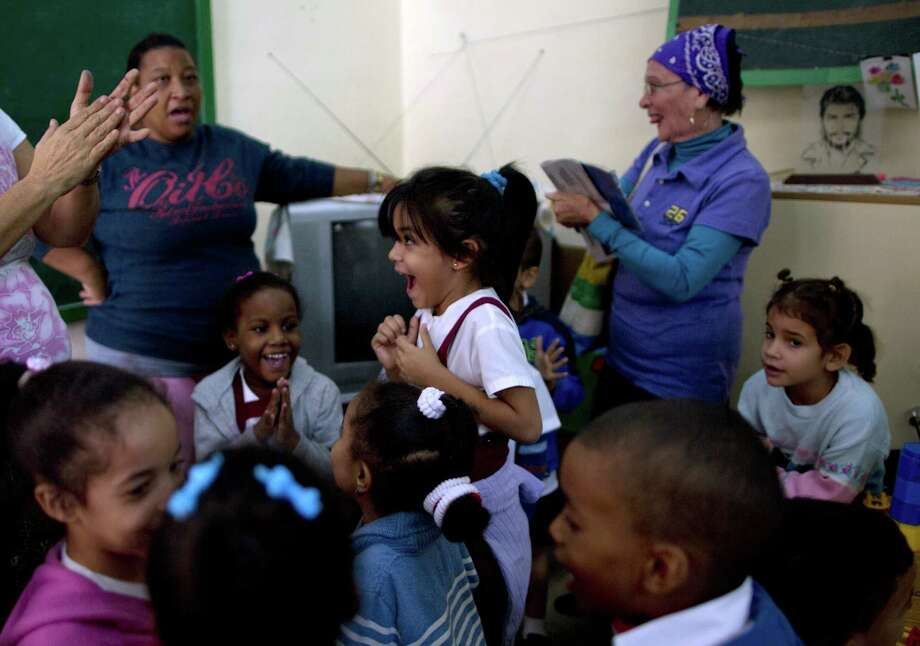 Students and teachers celebrate after listening to a live, nationally broadcast speech by Cuba's President Raul Castro about the country's restoration of relations with the United States, at a school in Havana, Cuba, Wednesday. Photo: Ramon Espinosa — The Associated Press  / AP