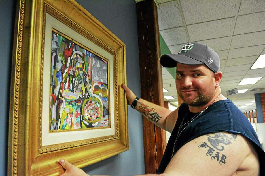 Mike Finnerty, The Register Citizen Artist of the Month for July 2014, hangs a piece of his work in the newsroom cafe at 59 Field St. Photo: Tom Caprood — The Register Citizen