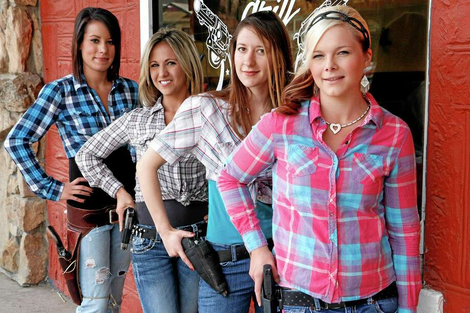 From left, waitresses Ashlee Saenz, Lauren Boebert, Jessie Spaulding and Dusty Sheets pose for a photo with their sidearms in front of the Shooters Grill in Rifle, Colorado. Photo: The Associated Press — Glenwood Springs Post Independent, Christopher Mullen  / Glenwood Springs Post Independent