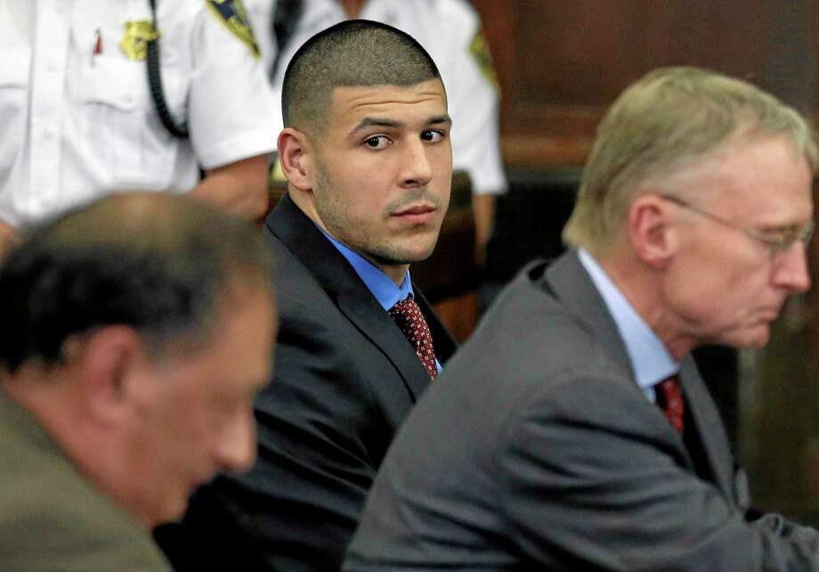 Former New England Patriots tight end Aaron Hernandez, center, looks toward defense attorneys James Sultan, left, and Charlie Rankin, right, during a June 24 hearing in Suffolk Superior Court in Boston. Photo: Steven Senne — The Associated Press  / Pool AP