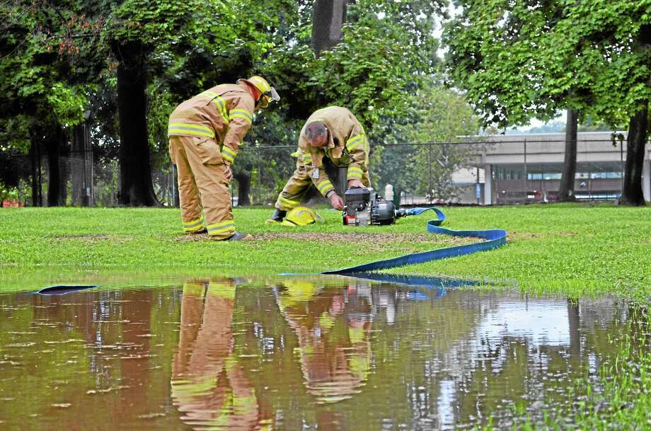 Firefighters work to pump water from a flooded section of grass behind Torrington's Coe Memorial Park Civic Center on Aug. 28, 2013. Photo: Tom Caprood—Register Citizen