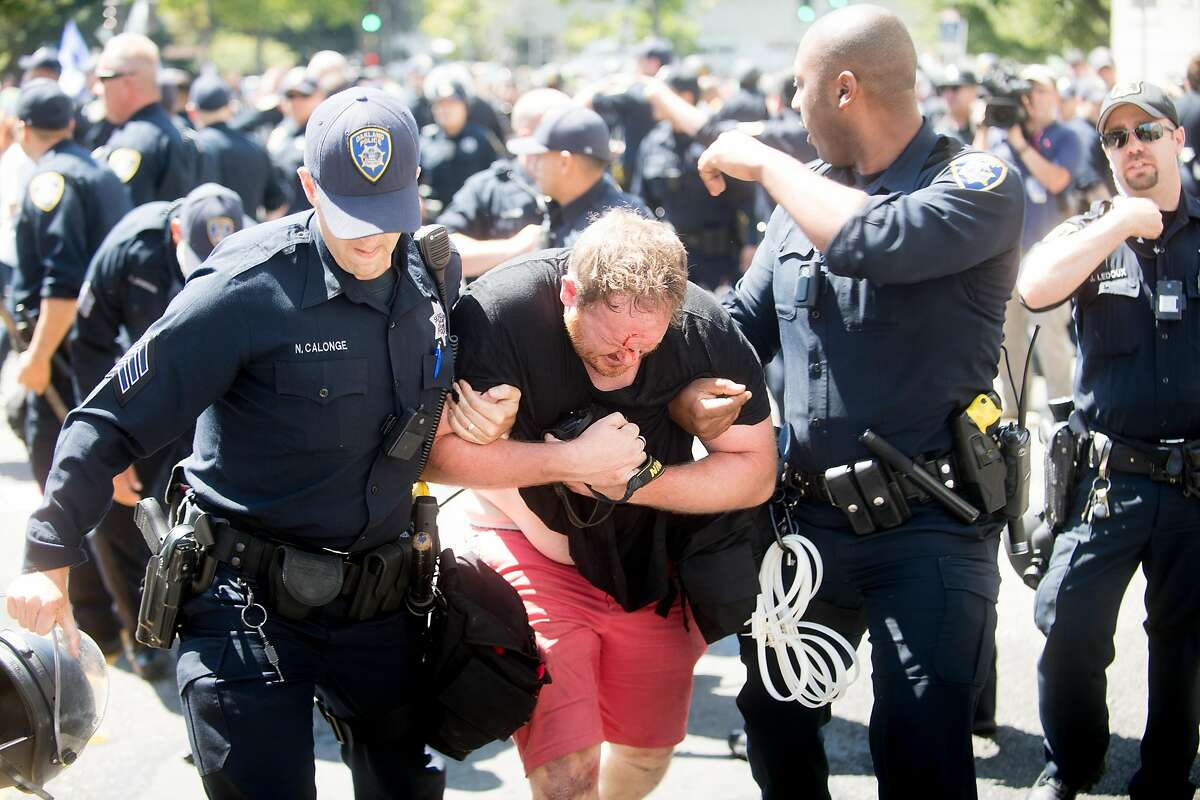 Police officers rescue a man attacked by protesters against conservative activists on Sunday, Aug. 27, 2017, in Berkeley, Calif.