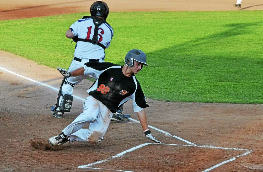 Terryville's Mike Milius slides around Torrington's Nick Andro to score the first run of the game in the top of the first inning. Photo: Pete Paguaga — Register Citizen