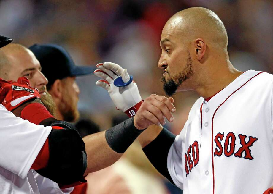 The Red Sox's Shane Victorino has his beard pulled by teammate Mike Napoli as he celebrates at the dugout after hitting a three-run homer against the Baltimore Orioles in the fifth inning of Tuesday's game. Photo: Elise Amendola  — The Associated Press  / AP