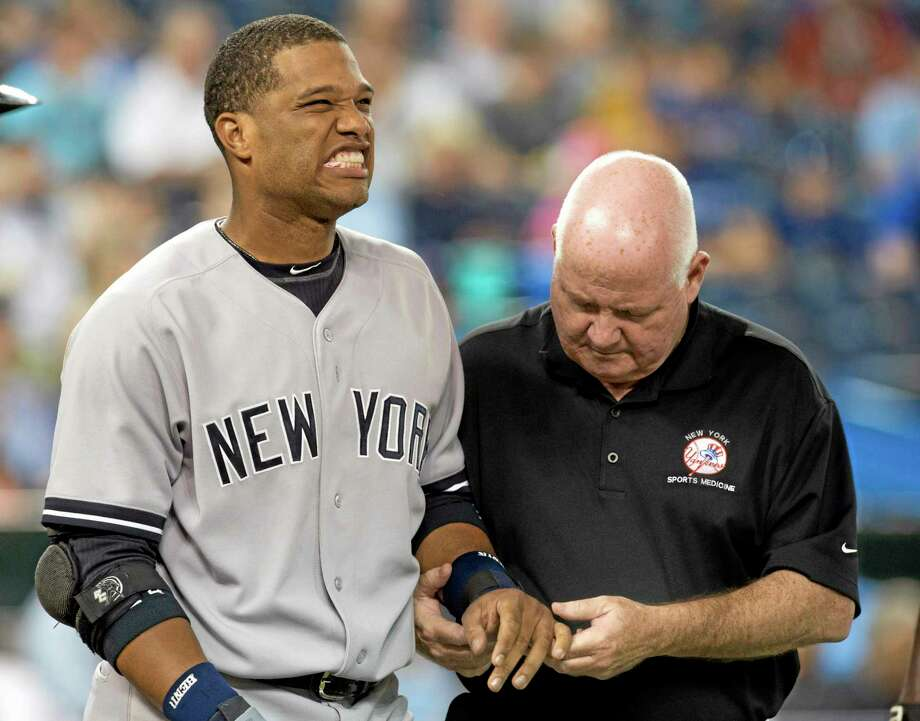 The Yankees' Robinson Cano is attended to by trainer Steve Donohue after getting hit on the hand by a pitch from Toronto Blue Jays starting pitcher J.A. Happ during the first inning of Tuesday's game in Toronto. Cano sustained a bruised left hand Photo: Frank Gunn — The Canadian Press/The Associated Press  / CP