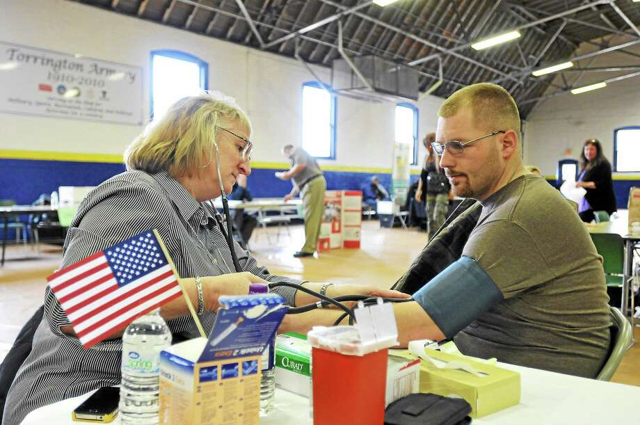 Laurie Gaboardi - Register Citizen Active-duty Army National Guard Specialist Grant Hagedorn Jr. gets his blood pressure taken by Linda Hetson, RN - Visiting Nurse Service, during FISH's third-annual Veteran Stand Down event in Torrington. Photo: Journal Register Co.