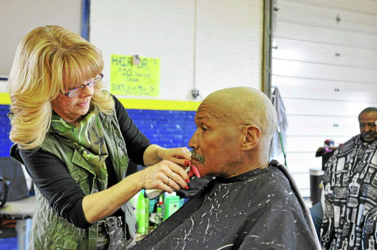 Laurie Gaboardi-Register Citizen U.S. Air Force aircraft mechanic Willie Crittenden gets a mustache and beard trim from Kerry Kocif of Hair Dr. during FISH's third-annual Veteran Stand Down event in Torrington.