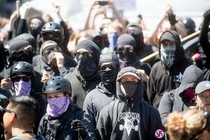 """Black bloc protesters gather in Martin Luther King Jr. Civic Center Park on Sunday, Aug. 27, 2017, in Berkeley, Calif. They and fellow counterprotesters chased off conservatives gathered for a """"No Marxism in America"""" rally."""