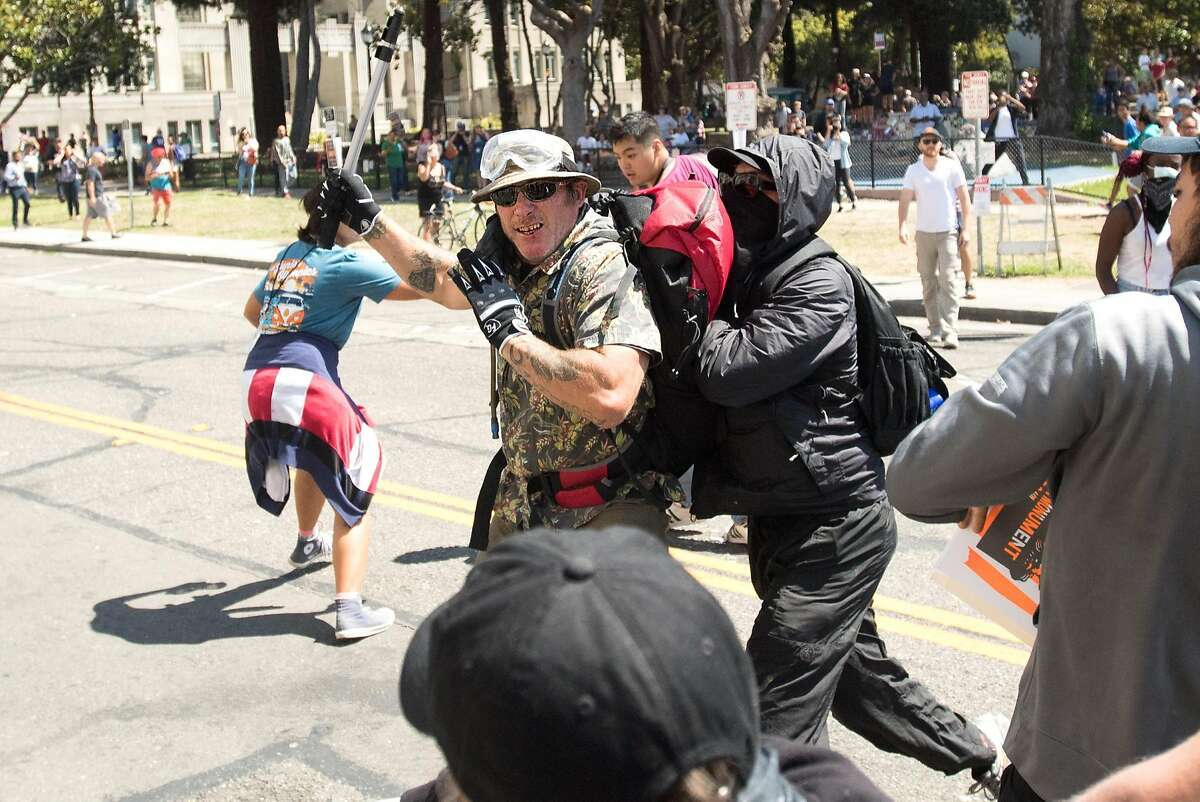 A black bloc protester pushes a conservative demonstrator in Martin Luther King Jr. Civic Center Park on Sunday, Aug. 27, 2017, in Berkeley, Calif. The conservatives had planned a