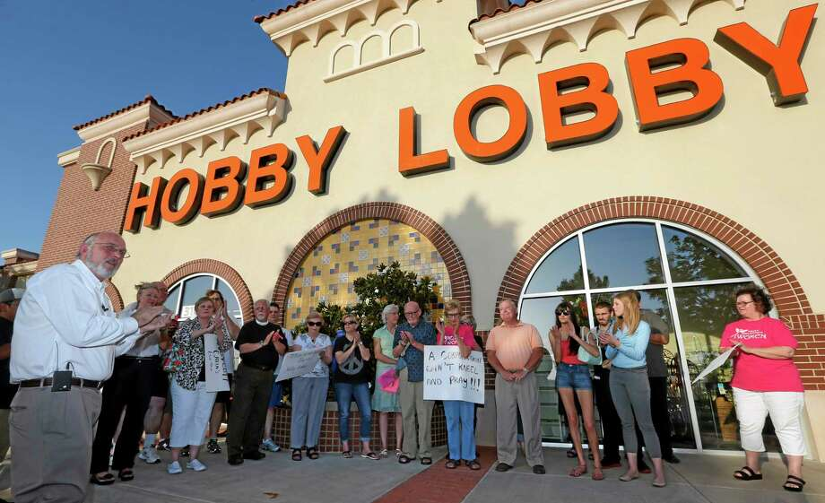 Rev. Bruce Prescott, left, applauds during a vigil outside a  Hobby Lobby store in Edmond, Okla., Monday, June 30, 2014, in reaction to the Supreme Court's decision that some companies like the Oklahoma-based Hobby Lobby chain of arts-and-craft stores can avoid the contraceptives requirement in President Barack Obama's health care overhaul, if they have religious objections. (AP Photo/Sue Ogrocki) Photo: AP / AP