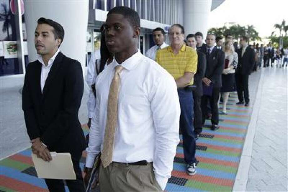 Luis Mendez, 23, left, a student at Miami Dade College, left, and Maurice Mike, 23, right, a student at Florida International University, wait in line at an internship job fair held by the Miami Marlins at Marlins Park in Miami. Photo: AP / AP