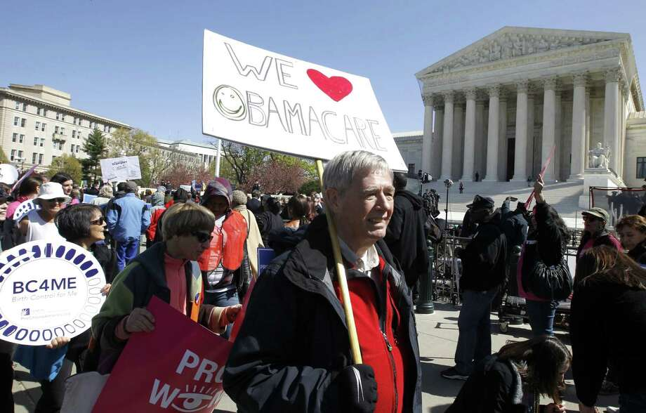 "Holding a sign saying ""We Love Obamacare"" supporters of health care reform rally in front of the Supreme Court in Washington, Tuesday, March 27, 2012, as the court continued hearing arguments on the health care law signed by President Barack Obama. Go ahead, call it Obamacare. Obamaís re-election campaign has lifted an unofficial ban on using the oppositionís derisive term for his health care law. Democratic activists have been chanting, ""We love Obamacare,"" in front of the Supreme Court. And the campaign is selling T-shirts and bumper stickers that proclaim: ""I like Obamacare."" (AP Photo/Charles Dharapak) Photo: AP / AP"