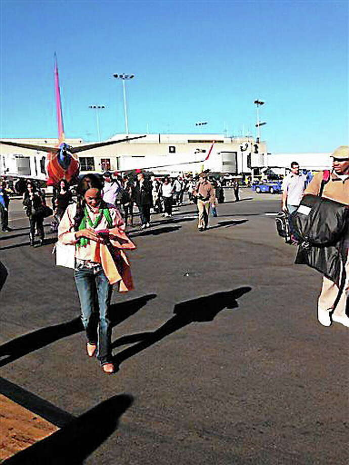 In this photo provided by Natalie Morin, people stand on the tarmac after being evacuated from Los Angeles International Airport, Friday, Nov. 1, 2013, in Los Angeles, after shots were fired at Terminal 3, prompting authorities to evacuate the terminal and stop flights headed for the city from taking off from other airports. (AP Photo/Natalie Morin) Photo: AP / Natalie Morin